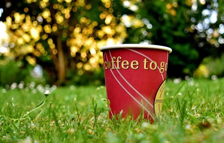 a red paper thermo cup, standing in grass (blurred background) with words ''coffee to go'' in yellow