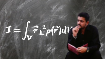 chalkboard in the background with a lengthy formula written on it. A blurred image of a man sitting in front of the board, book in hand, other hand at mouth/chin. Looking off into the distance in thought.
