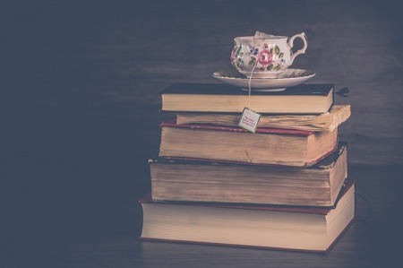 a hazy view of an antique tea cup with saucer resting on top of a stack of old weathered books. The string from the tea bag drapes down, over the top books, showing the tag at the end of the string