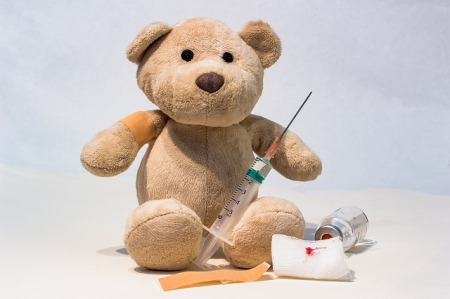 a teddy bear sitting with a bandaid on its right upper arm, long needled syringe in lap, gauze pad, bandaid and tipped over injection bottle surroud