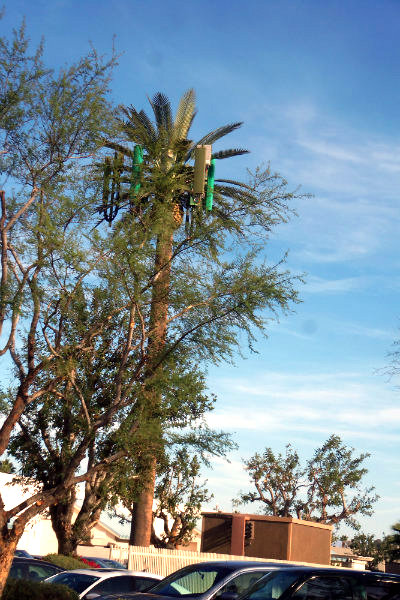 an artificial palm tree with cylinders atached to its foliage