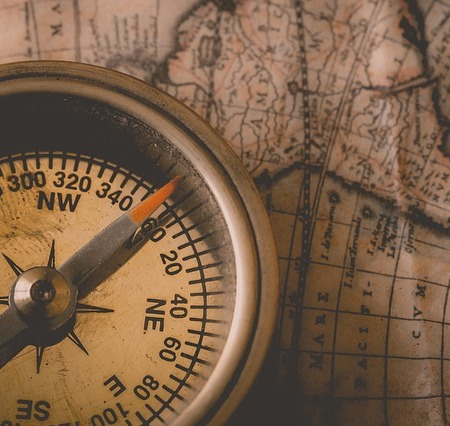 a close up of a compass resting on a map