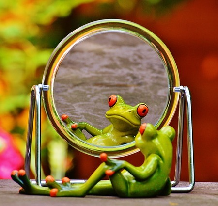 an animated frog, leisurely hanging out in front of a round mirror on its stand