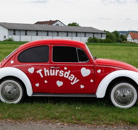 red and white vw beetle with Thursday and hearts painted on the side.
