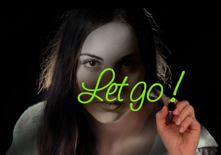 A lady facing the camera, dark background. Wrote the words Let go! in front of her face.