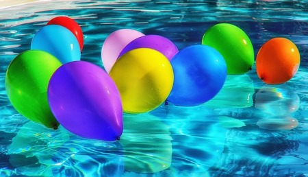ten colorful balloons floating on blue water