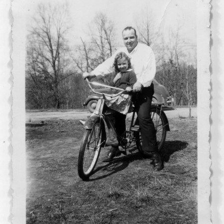 black and white vintage image of a man on a bicycle with child sitting on crossbar, an old auto in background.