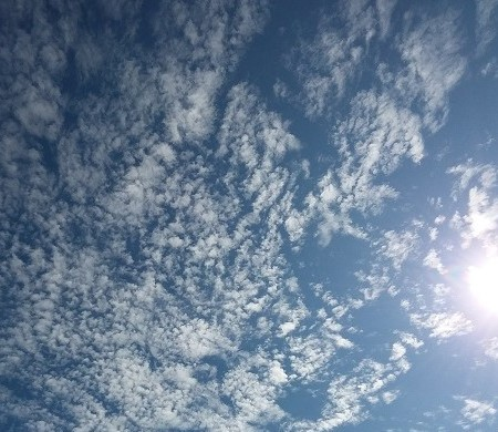 Popcorn clouds, blue sky with sun entering from the right