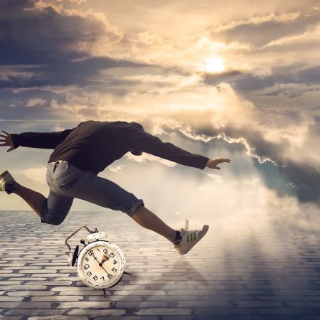 A person jumping over an alarm clock with light coming through clouds in the background