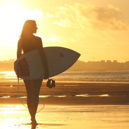 A female, carrying surfboard, walking towards the water as the sun rises
