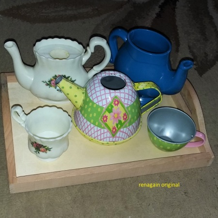 3 toy tea pots and two toy tea cups on a wooden tray
