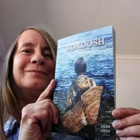 image of myself, holding a copy of the book, Soroosh, by Laleh Chini